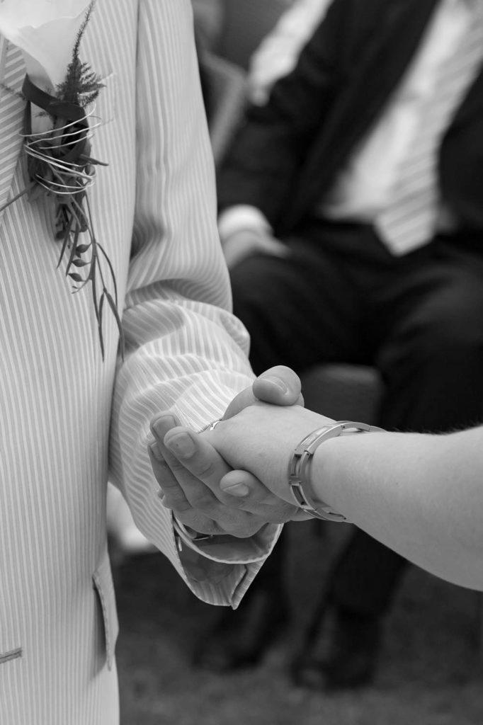 Der Bräutigam hält die Hand der Braut